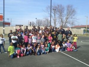 Former Mizzou football players take a group photo with children from the Columbia, Mo. Boys and Girls Club Friday, April 5, 2013.